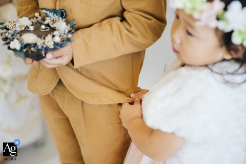 Raffino Ocean wedding photographer | Brother and Sister Love at the ceremony | Young flower girl holding on to Jacket