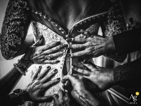 Fotografia dnia ślubu Firenze | czarno-biały szczegół Obraz wielu rąk pomagających pannie młodej w trakcie przygotowań