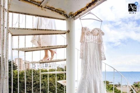 Mersin wedding photography - the Bride and her bridal dress hanging as she climbs spiral stairs outside at the beach