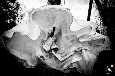 Poggio degli Olivi, Montevettolini (Pistoia) wedding photographer | detail Photo of the bride's dress and her shoes while she is on a swing