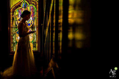 Smather's Library, University of Florida Gainesville Wedding Photography | The bride pauses at the top of the stairs in her Mother's home and looks at her engagement ring, backlit by yellow-green stained glass