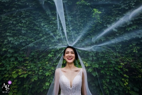 China wedding photographer froze the action in this photo of the brides veil being blown about in front of a large bush