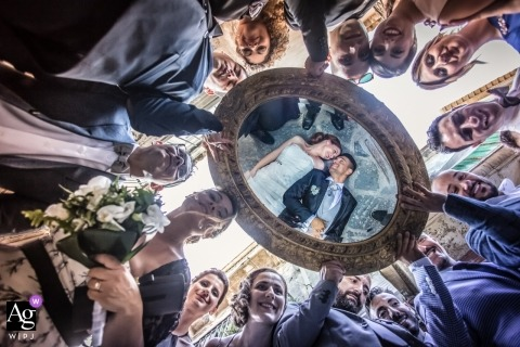 Sicily wedding photographer designed this photo of the bride and grooms reflection being caught by a mirror being held by guests at their Siracusa wedding at Il Mirto - rosolini