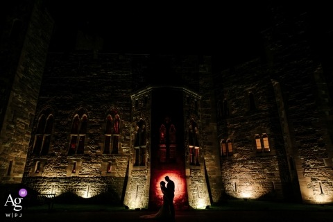 England wedding reportage photographer designed this portrait of the bride and groom standing in front of the Peckforton Castle at night