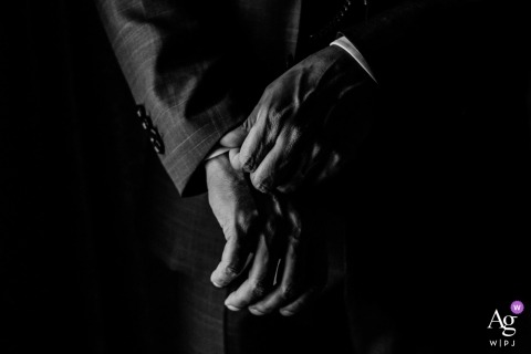 detail of man's hands readying his sleeves for the wedding