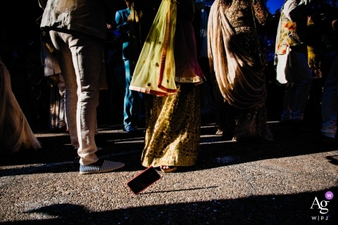 Vietnam wedding photographer caught this photo of a phone hitting the pavement as the wedding guests walked to the ceremony - PHUQUOC WPJA