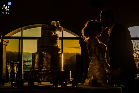 Northern California wedding photographer froze the moment of the groom kissing the bride on the forehead next to the cake at their San Francisco wedding reception