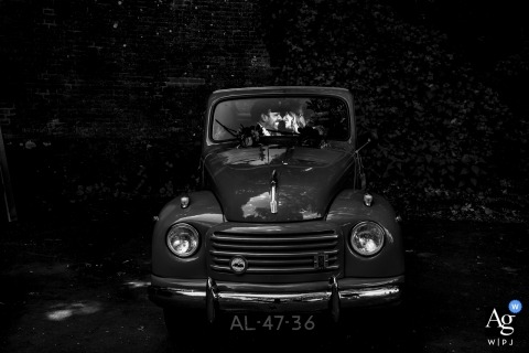 Netherlands wedding photographer caught the action in this black and white photo of the bride and groom kissing in the front seat of a classic truck at Fort Vechten