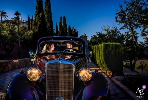 Spain wedding photographer shot this portrait of the bride and groom driving off in a classic purple car