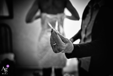 This black and white photo of the bride getting her dress laced up was captured at the Cuccaro Club by a Liguaria wedding photographer