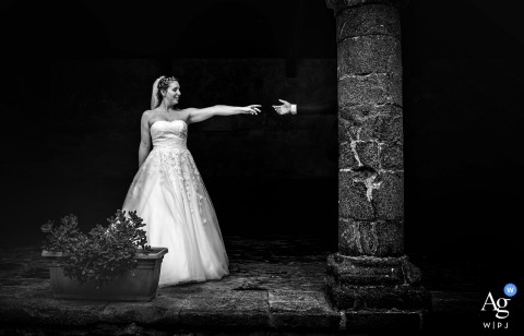 Liguaria wedding photographer designed this black and white portrait of the bride and groom reaching for each others hands in Levanto