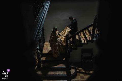 Il fotografo di matrimoni spagnoli ha catturato questo scatto dall'alto della sposa che scende le scale mentre lo sposo la aiuta con il suo vestito a Chiva