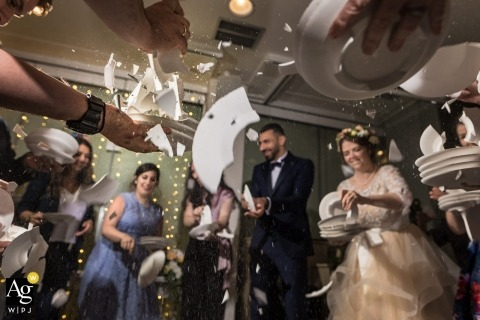 Santorini wedding photographer caught this action filled shot of the bridal party smashing dishes at the reception