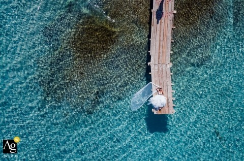 This aerial drone shot of the bride and groom sunning themselves on a pier over crystal clear water was captured by a Tuscany wedding photographer