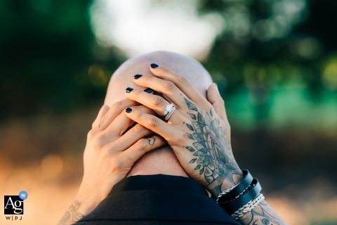 San Jose wedding photographer created this beautiful image of the bride cradling the grooms head while showing off her engagement and wedding rings on her tattooed hands
