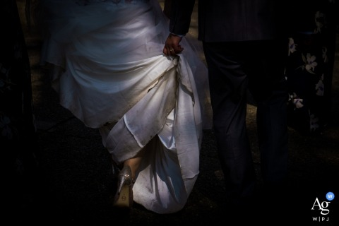 Wedding detail of bride's dress lit by natural light as she and the groom walked to the ceremony location after raining.