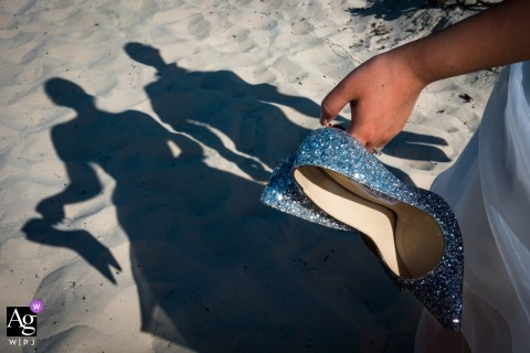 Detail of the bride's blue shoes and a shadow of the couple on the sand of Mexico