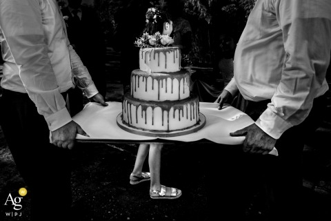 Hesse wedding photographer designed this humorous photo of a wedding kid standing in the perfect location to give the appearance of the cake having legs as the caterers carried it past