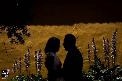 This silhouette photo of the bride and groom embracing in front of a yellow stucco wall was shot by a Madrid wedding photographer