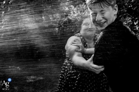 Hesse wedding photographer froze the action in this black and white photo of wedding guests playing in spraying water at the reception