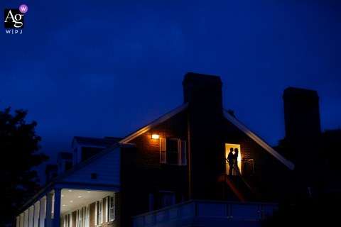 Evening wedding portrait of a couple posing on a staircase at the Buell Mansion in Denver as a storm looms above.