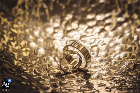 Hunan wedding photographer designed this detail image of the bride and grooms wedding bands resting on a metallic surface