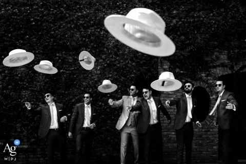 Antica Fattoria di Paterno Tuscany award-winning, black and white wedding portrait of the groom with his groomsmen tossing hats toward the camera