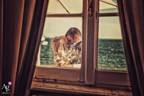 Fotograf ślubny Ligurii uchwycił delikatny portret młodej pary, która obejmuje za zamkniętym oknem