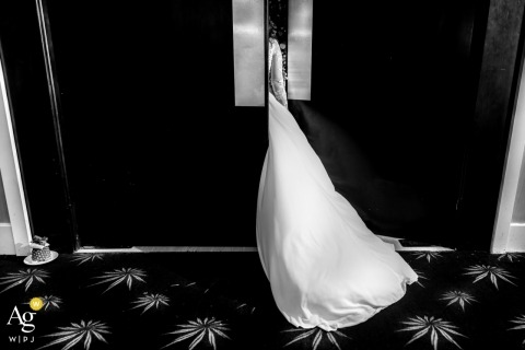 Vietnam wedding photographer froze the moment of the brides dress train getting stuck in the door in this black and white photo