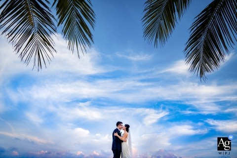 Nha Trang bride and groom kiss under a bright blue sky as palm leaves frame the shot in this image captured by a Vietnam wedding photographer