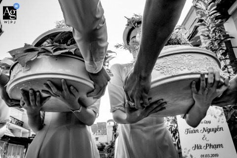 Vietnam wedding photographer froze the action in this image of the caterers getting some help carrying in the food platters for the Ho Chi Minh reception