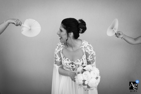 Calabria wedding photographer froze this joyful moment in this black and white photo of the bride laughing as she got cooled down with fans before the ceremony at Chiesa di Maria Ss.Delle Grazie