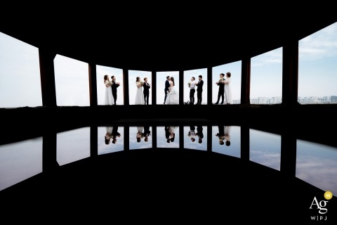Zhejiang wedding photographer designed this artistic photo of the bridal party standing in different window panes in front of a cloudy sky