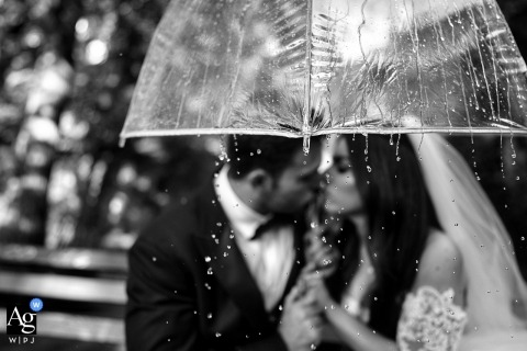 Black and White wedding portrait of the bride and groom under an umbrella at Fort Tryon Park
