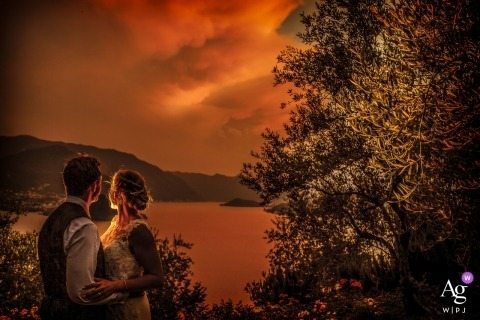 Lombardy wedding photographer designed this bridal portrait of the bride and groom standing in front of a lake as the sun makes everything golden around them at varenna lago como