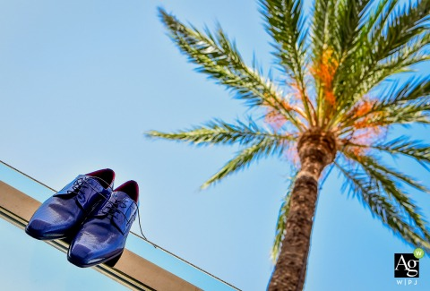 Murcia Spain wedding day detail photo | Shoes of the groom hanging on glass below a palm tree and blue sky