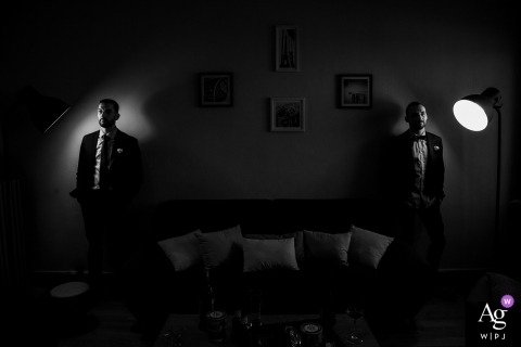 This black and white photo of two men standing on either side of a couch was created by a Vosges wedding photographer
