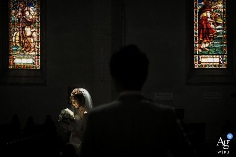 A spotlight illuminates the bride as she stands in front of stained glass windows while the groom approaches in this photo created by a Tuscany wedding photographer