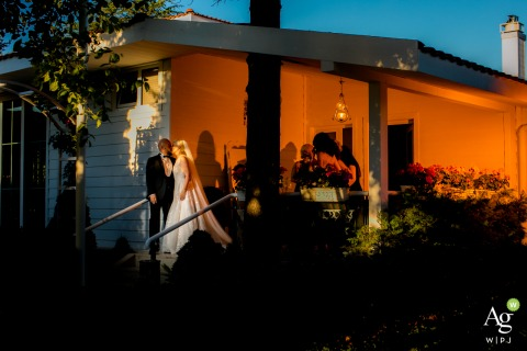Turkey wedding photo - İncek Garden | Couple standing in front of the small house and kissing