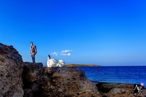 Attica wedding photographer crafted this bridal portrait of the bride and groom standing on a windy cliff next to a brilliant blue sea