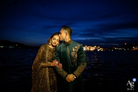 Mumbai wedding photographer created this image of the bride and groom embracing in front of a night time city sky line