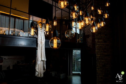 Swiss Hotel Bosphorus wedding venue detail photo | A wedding dress hanging on the 1st floor behind the bulbs