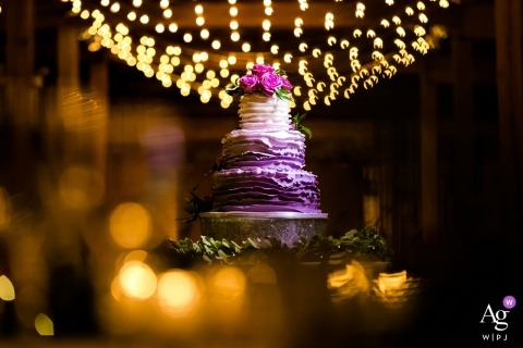 Chicago wedding photographer created this detail image of a purple three tier wedding cake resting on a table under strands of light