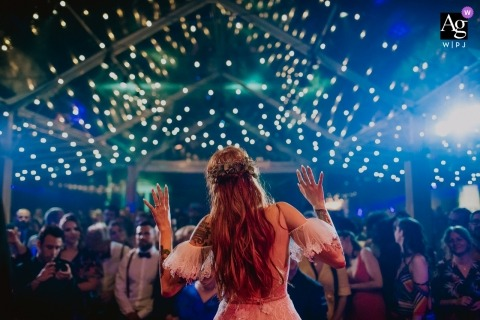 This photo of the bride standing in front of the wedding guests under a canopy of twinkle lights was created by a Rio Grande du Sol wedding photographer