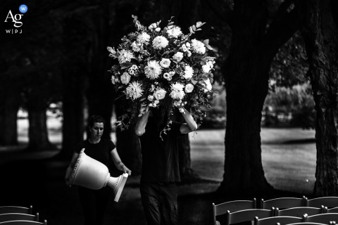 An Ontario wedding photographer shot this black and white photo of the florist setting up a huge floral arrangement at an outdoor ceremony