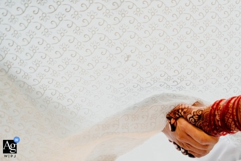 This detail image of the bride and groom holding hands through a curtain during their ceremony was created by an Ontario wedding photographer
