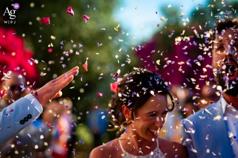 Hacienda de San Rafael, Spain Wedding Photo of Confetti petals flying over the bride and groom after the outdoor ceremony.