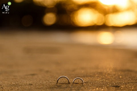Caracas detail photography - Wedding rings half buried in the sand at sunset