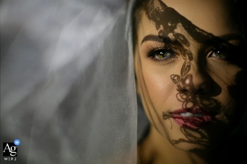 Brazil wedding photographer designed this portrait of the bride looking straight at the camera as her veil casts shadows on her face
