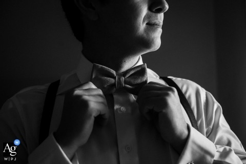 Brazil wedding photographer created this black and white image of the groom straightening his bowtie before the ceremony